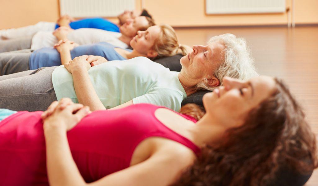 Gruppe mit Seniorin entspannt bei Atemübung im Yoga Kurs